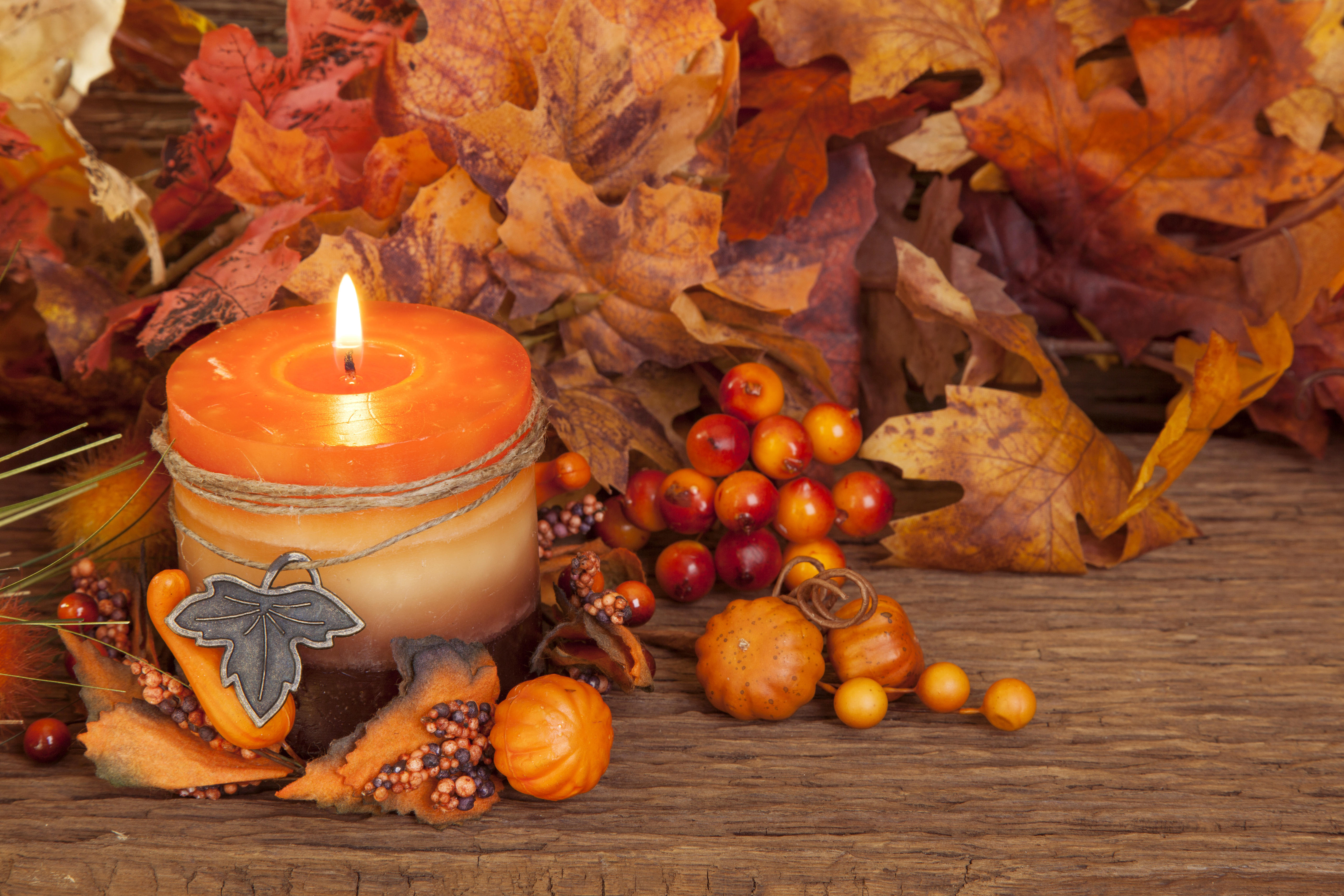 Pumpkin orange candle surrounded by various Autumn items